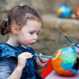 Pintura da menina da criança com cores na abóbora Fotos de Stock Royalty Free