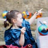 Pintura da menina da criança com cores na abóbora Fotografia de Stock