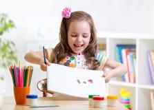Pintura da menina da criança e pintura da exibição dentro imagem de stock royalty free