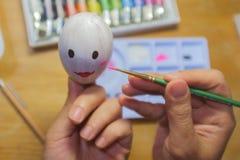 Pintura da menina em ovos à vista da Páscoa Imagens de Stock Royalty Free