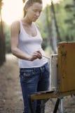 Pintura da mulher na lona em Forest Clearing fotos de stock royalty free