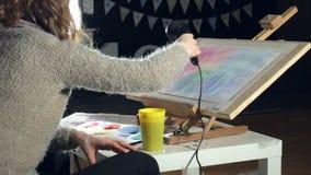 A pintura das mulheres adultas com pinturas coloridas da aquarela e seca com um secador de cabelo em uma escola de arte