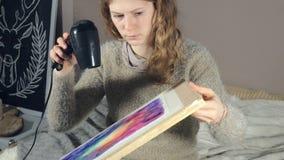A pintura das mulheres adultas com pinturas coloridas da aquarela e seca com um secador de cabelo em uma escola de arte filme