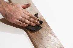 Pintura de óleo masculina da fricção da mão na parte de madeira foto de stock