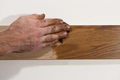 Pintura de óleo masculina da fricção da mão na parte de madeira imagem de stock royalty free