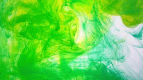 Pintura de color verde amarillo que remolina en agua Movimiento suave de la tinta en el agua