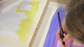 Pintura de dos mujeres adultas con las pinturas acrílicas coloreadas en un cierre de la escuela de arte para arriba