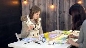 Pintura de dos mujeres adultas con las pinturas acrílicas coloreadas en una escuela de arte