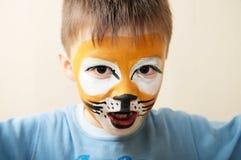 Pintura de la cara de los niños El muchacho pintado como tigre o el león feroz cerca compone al artista Preparing para el funcion Foto de archivo