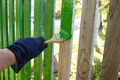 Pintura de la cerca por un cepillo Fotos de archivo