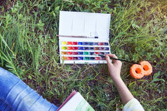 Pintura de la chica joven que se sienta en hierba en verano Fotografía de archivo
