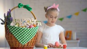Pintura de la colegiala y poner el huevo coloreado en la cesta, atmósfera del día de fiesta metrajes