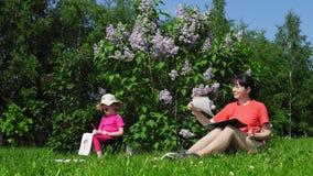 Pintura de la familia, de la madre y de la hija al lado de arbustos de lila de florecimiento en el parque metrajes