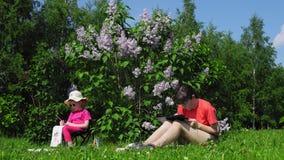 Pintura de la familia, de la madre y de la hija al lado de arbustos de lila de florecimiento en el parque almacen de video