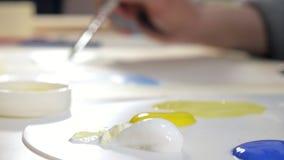Pintura de las mujeres adultas con las pinturas acrílicas coloreadas en un cierre de la escuela de arte para arriba