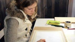 Pintura de las mujeres adultas con las pinturas acrílicas coloreadas en una escuela de arte