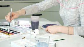 Pintura de las mujeres adultas con las pinturas coloreadas de la acuarela en un estudio casero almacen de video
