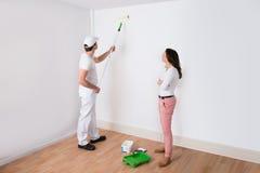 Pintura de Looking At Painter del ama de casa foto de archivo libre de regalías