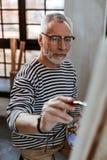 Pintura de ojos oscuros del artista en lona mientras que teniendo inspiración imágenes de archivo libres de regalías