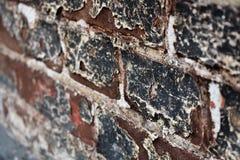 Pintura de piedra vieja resistida del negro de la pared de ladrillo que pela apagado la ciudad blanca anaranjada envejecida cemen fotos de archivo libres de regalías