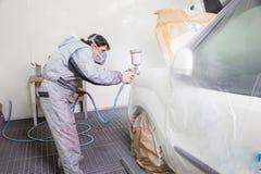 A pintura de pulverização do pintor do corpo de carro na carroçaria parte Fotos de Stock Royalty Free