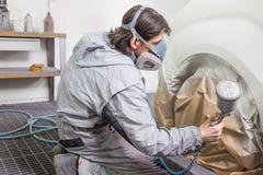 A pintura de pulverização do pintor do corpo de carro na carroçaria parte Imagem de Stock Royalty Free