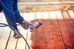 Pintura de pulverização do trabalhador sobre a madeira da madeira Trabalhador da construção com arma de pulverizador Fotos de Stock
