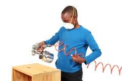 Pintura de pulverizador do menino com um injetor de pulverizador Fotografia de Stock