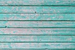 A pintura de turquesa rachou-se na parede de madeira velha fotografia de stock royalty free