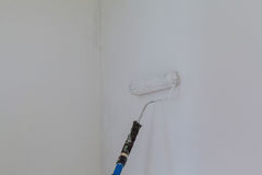 Pintura de una pared áspera por el rodillo de pintura y el látex blanco Esta imagen común contiene un rodillo de pintura Fotografía de archivo libre de regalías