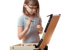 Pintura del adolescente de la muchacha en un caballete aislado en el fondo blanco Muchacha rubia con los vidrios Fotos de archivo
