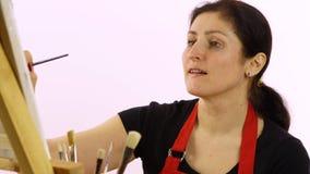 Pintura del artista de la mujer con la brocha La mujer dibuja una imagen El artista en un fondo blanco dibuja en un aceite del ca almacen de video