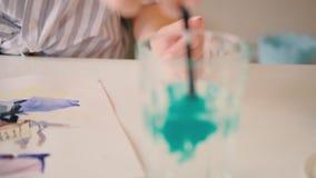 Pintura del artista que sumerge la pintura del cepillo que revuelve el agua almacen de metraje de vídeo