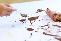 Pintura del bebé con las manos con el chocolate Foto de archivo