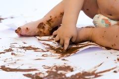 Pintura del bebé con las manos con el chocolate Imagen de archivo libre de regalías