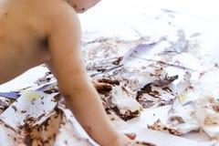 Pintura del bebé con las manos con el chocolate Fotos de archivo