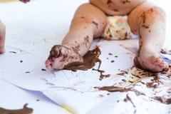 Pintura del bebé con las manos con el chocolate Fotografía de archivo libre de regalías
