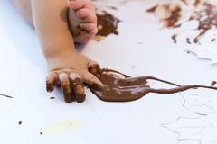 Pintura del bebé con las manos con el chocolate Imagen de archivo