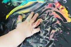 Pintura del bebé con sus manos Fotos de archivo