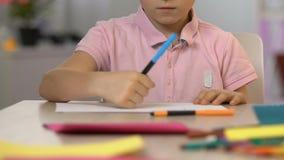 Pintura del muchacho con la pluma de extremidad de fieltro, escuela de arte para los niños talentosos, tiempo libre almacen de metraje de vídeo