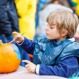 Pintura del muchacho del niño con colores en la calabaza Foto de archivo libre de regalías