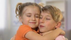 Pintura del muchacho, hermana que corre al hermano que lo abraza y que besa, amor de los hermanos almacen de video