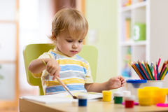 Pintura del niño pequeño en clase creativa adentro Fotografía de archivo libre de regalías