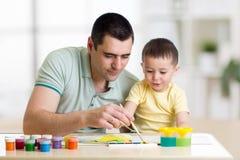 Pintura del padre y del niño junto El papá enseña hijo a cómo pintar correcto y hermoso en el papel Creatividad de la familia y foto de archivo libre de regalías
