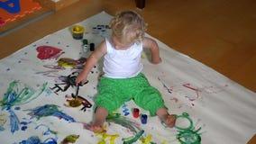 Pintura divertida de la niña en piso en casa metrajes