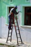 Pintura do homem a parede da casa imagens de stock royalty free