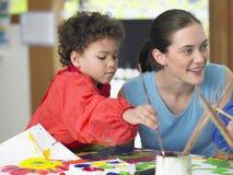 Pintura do menino ao lado de Art Teacher Fotografia de Stock