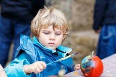 Pintura do menino da criança com cores na abóbora Imagem de Stock Royalty Free