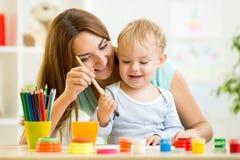 Pintura do menino da mamã e da criança junto em casa Fotografia de Stock