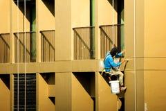 Pintura do pintor na construção alta da elevação fotografia de stock royalty free